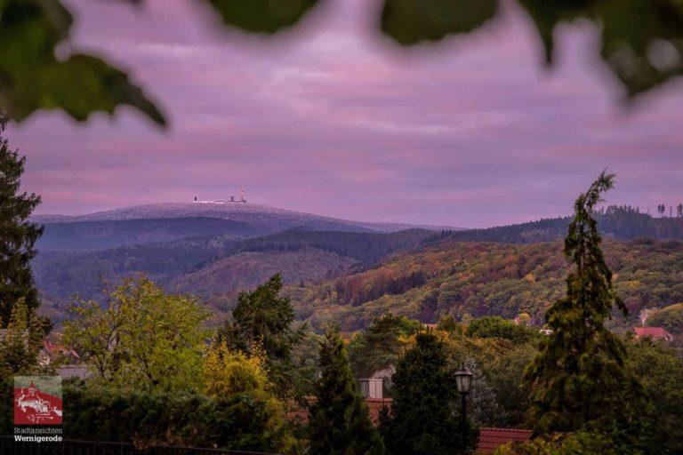 Sonnenaufgang im Herbst mit Schnee auf dem Brocken und bunter Laubfärbung in Wernigerode.
